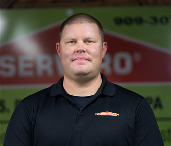 a man in front of a green SERVPRO background