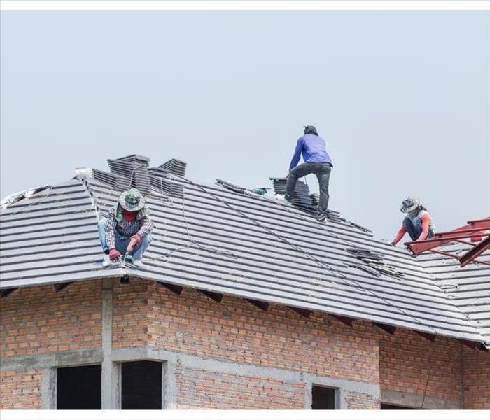 Workers installing concrete tiles on the roof while roofing in construction site
